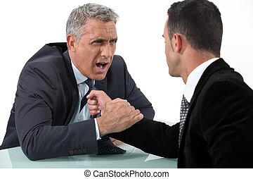 Businessmen fighting at desk