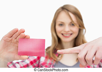 Woman holding a loyalty card while showing it with a finger...