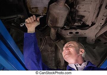 Smiling mechanic repairing the below of a car
