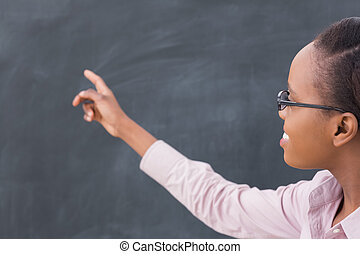 Black teacher pointing the blackboard in a classroom