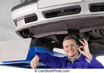 Smiling mechanic doing a gesture with his hand in a garage