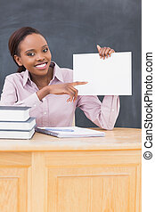 Black teacher holding a blank paper while sitting at desk in...