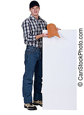 Roofer stood with tile and blank poster