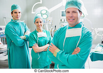 Surgical team with arms crossed smiling in an operating...