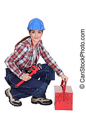 A female construction worker holding a wrench