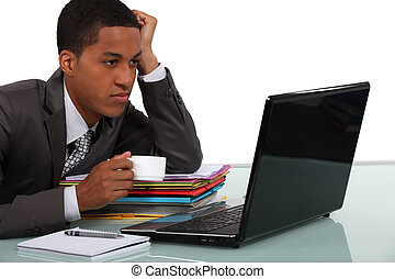 Young businessman taking a break in front of his laptop