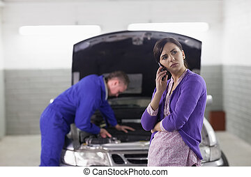 Client holding a mobile phone next to a car in a garage