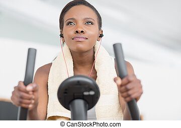 Low angle view of a black woman doing exercise bike in a...