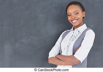 Teacher smiling with arms crossed in a classroom
