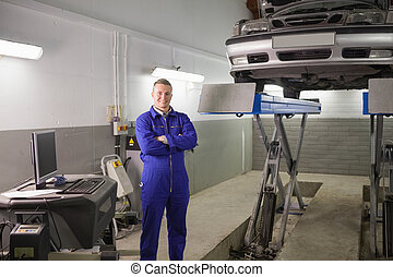 Smiling mechanic standing next to a car in a garage