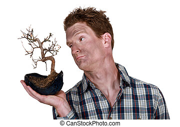 man covered with dirt holding a dead plant
