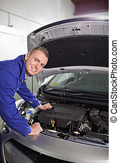 Mechanic looking at camera om a garage