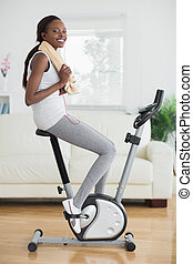 Black woman on an exercise bike smiling in a living room