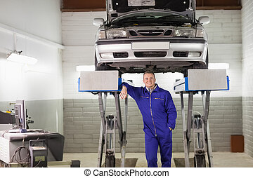 Smiling mechanic leaning on a machine below a car in a...