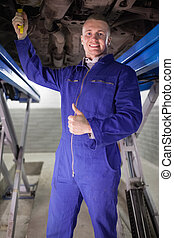 Man repairing a car with his thumb up in a garage