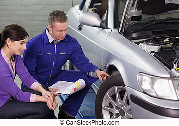 Mechanic touching the car wheel next to a client in a garage