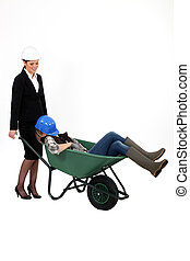 Woman pushing sleepy colleague in a wheelbarrow