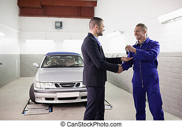 Mechanic giving car key while shaking hand to a client in a...