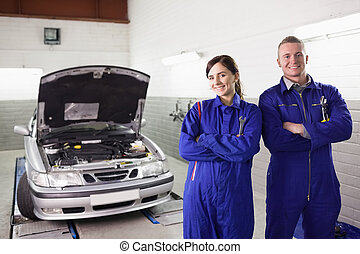 Smiling mechanics with arms crossed next to a car in a...