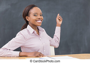 Black teacher showing the blackboard in a classroom