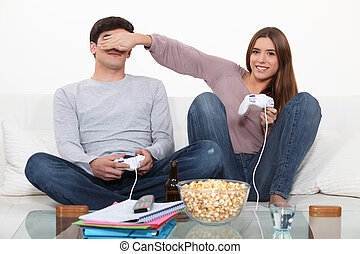 couple playing video game and eating popcorn