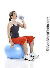 Relax - Beautiful woman seated on a core ball and drinking...