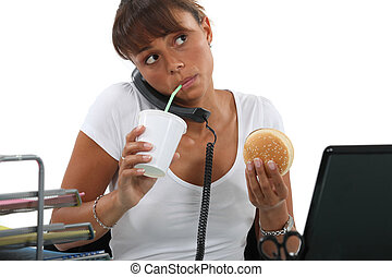 young woman eating hamburger and drinking out of a straw...
