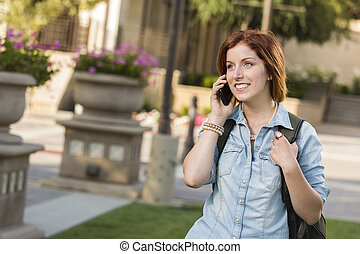 Young Female Student Walking Outside Using Cell Phone