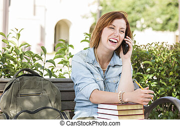 Young Female Student Outside Using Cell Phone Sitting on Bench