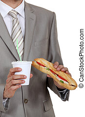 Businessman holding sandwich and soft drink