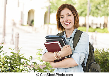 Smiling Young Female Student Outside with Books