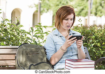 Stunned Young Female Student Outside Texting on Cell Phone