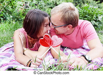 Young Couple with Candy Hearts on Picnic - Young Couple...