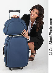 Woman squatting with suitcase