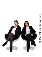 Businesswomen sitting side by side