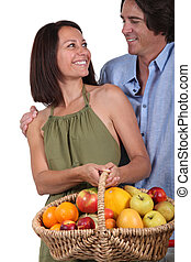 couple with basket of fruits