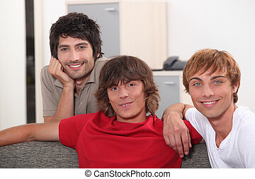 Three male students gathered on the sofa