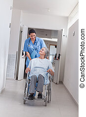 Nurse pushing a patient in a wheelchair in hospital ward