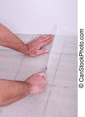 Man cutting underlay