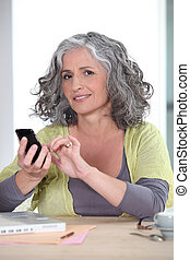Grey-haired woman sending text message