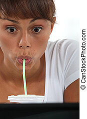 Expressive woman having a drink with a straw