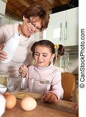 Child helping her grandmother make pancakes