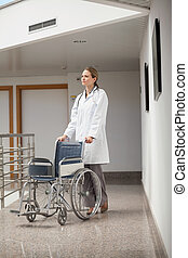 Serious doctor pushing a wheelchair in the corridor in...