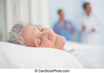 Elderly patient sleeping on a bed next to a doctor in...