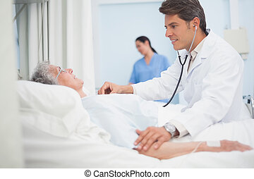 Doctor auscultating a patient in hospital ward