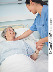 Patient smiling to a nurse while holding her hand in...
