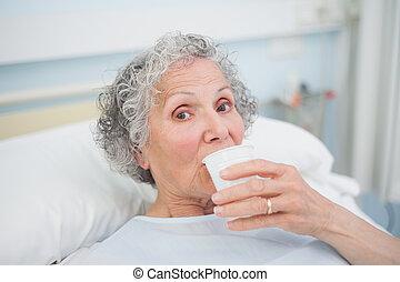 Elderly patient drinking in hospital ward