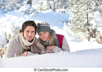 Couple laying on snowy hillside