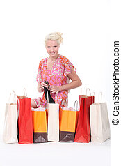 Excited blond woman going through her purchases