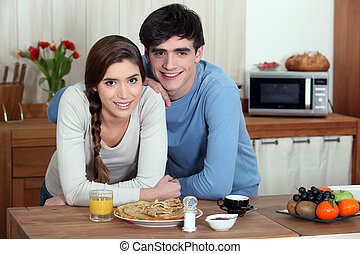 Young couple having pancakes for breakfast